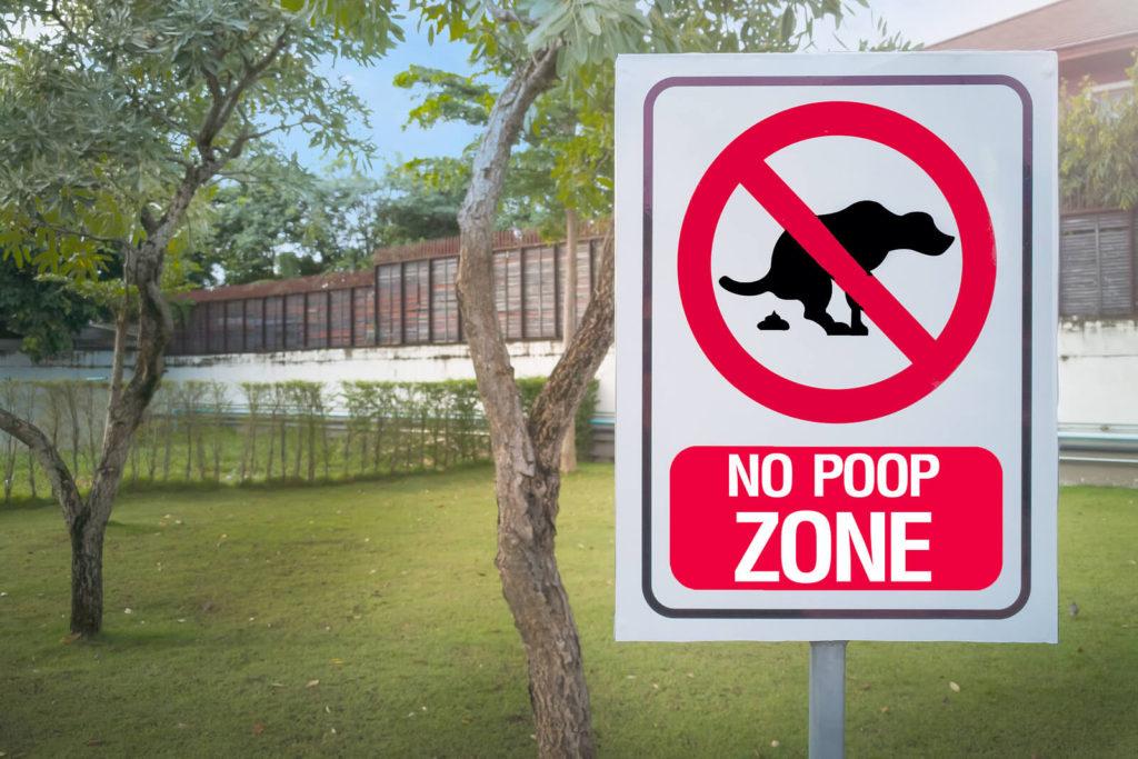 no poop zone sign near a grassy area