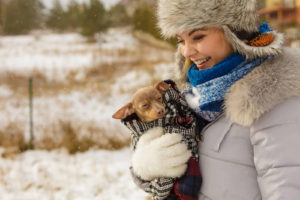 woman holding a small dog in the snow